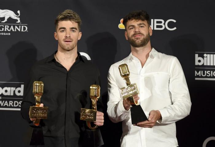 """Andrew Taggart, left, and Alex Pall of """"The Chainsmokers"""" pose in the press room with the awards for top dance/electronic artist, top dance/electronic song for """"Something Just Like This"""" and top dance/electronic album """"Memories...Do Not Open"""" at the Billboard Music Awards"""