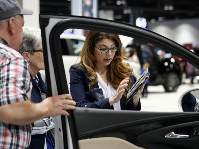 In this March 28, 2019, photo, a salesperson uses a tablet to find a car for prospective buyers as they look over a 2019 Encore sports-utility vehicle at the Buick display at the auto show in Denver