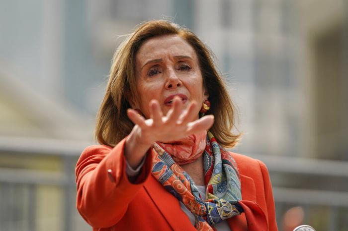 House Speaker Nancy Pelosi gestures while speaking about her visit to a hair salon.