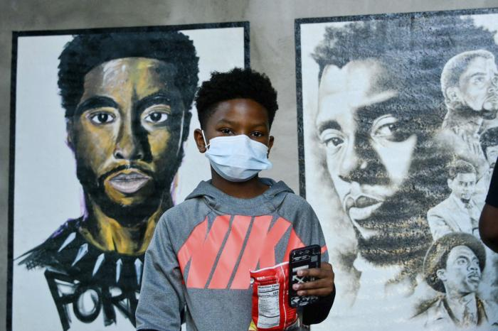 A boy stands in front of two paintings of Chadwick Boseman during the opening of an art exhibit honoring the actor in his hometown of Anderson, S.C.