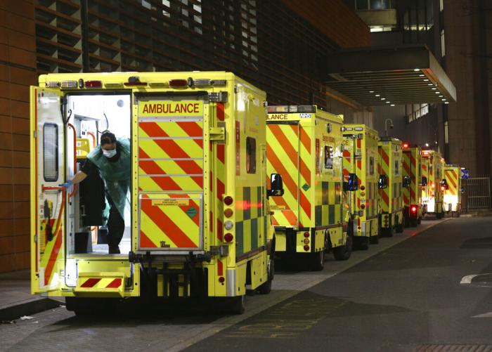 A row of ambulances are parked outside the Royal London Hospital in London on Tuesday, Dec. 29, 2020.