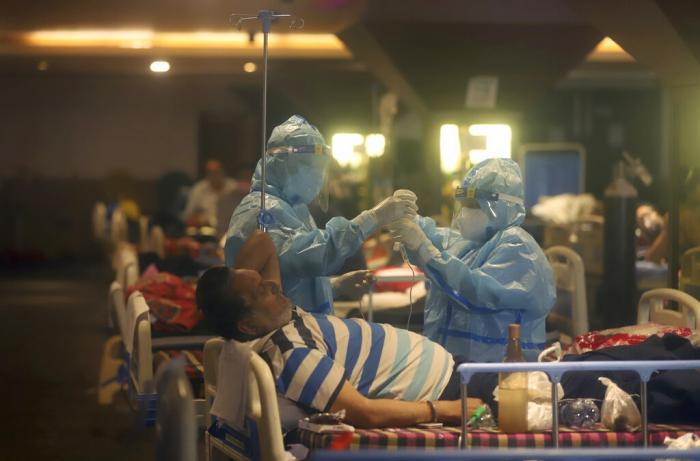 Health workers attend to COVID-19 patients at a makeshift hospital in New Delhi, India. COVID-19 infections and deaths are mounting with alarming speed in India with no end in sight to the crisis.