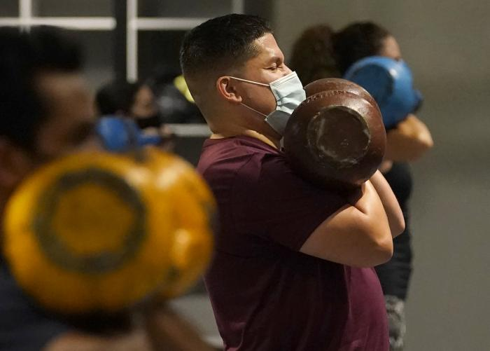 Juan Avellan, center, and others wear masks while working out in an indoor class at a Hit Fit SF gym amid the coronavirus outbreak in San Francisco.